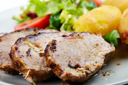 Closeup of a baked tenderloin with garnish of potatoes, lettuce and tomatoes on a plate Stock Photo - 17324677