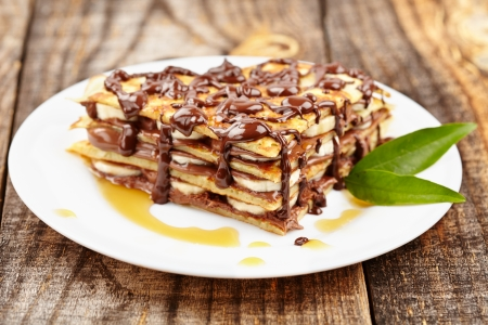 Stack of pancakes with banana slices and chocolate syrup on a plate photo