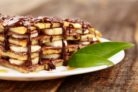 flapjacks: Stack of pancakes with banana slices and chocolate syrup on a plate