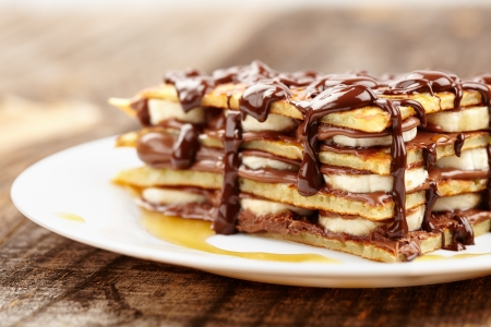 Stack of pancakes with banana slices and chocolate syrup on a plate Stock Photo - 17324566