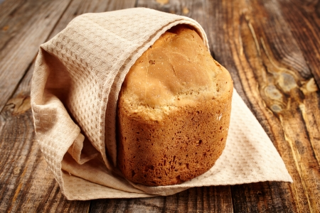 Homemade bread in a towel on a wooden board Stock Photo - 17324680