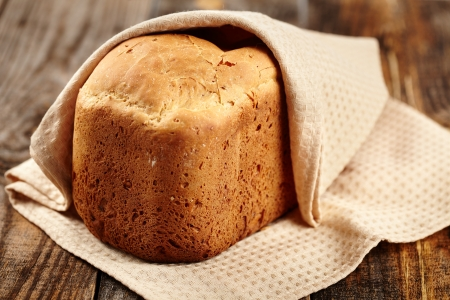 Homemade bread in a towel on a wooden board Stock Photo - 17324679