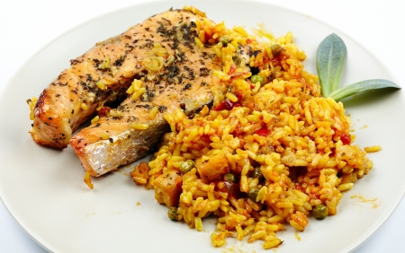 Red salmon garnished with rice, peas and other vegetables on a plate Stock Photo - 17324532