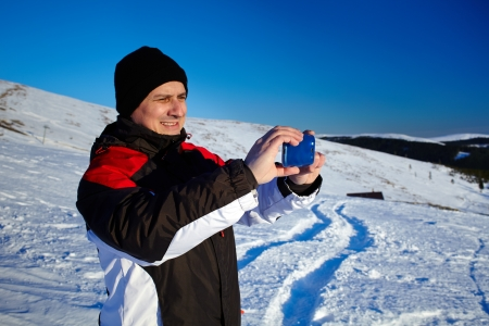 Tourist shooting the beautiful winter landscape with his mobile phone Stock Photo - 17324564