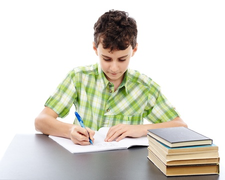 Caucasian student boy at his desk writing for homework photo