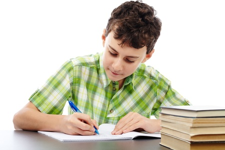 Caucasian student boy at his desk writing for homework Stock Photo - 17630406