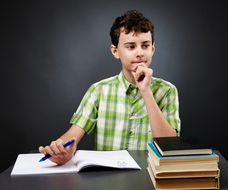 Caucasian student boy at his desk writing for homework Stock Photo
