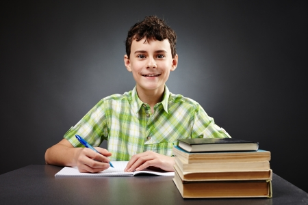 Caucasian student boy at his desk writing for homework Stock Photo - 17605331