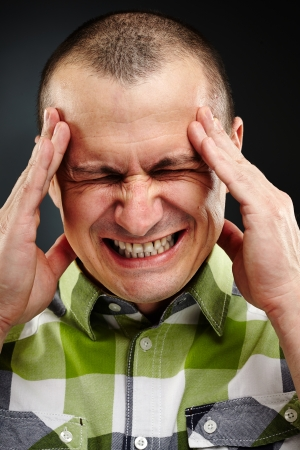 Closeup of a man with strong headache over gray background photo