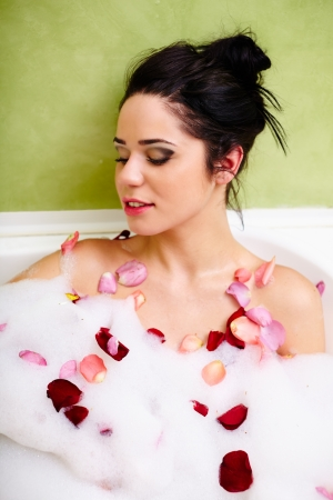 Young brunette woman in the bath tub with foam, relaxing Stock Photo - 17605319