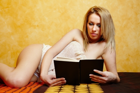 Young glamorous woman lying in bed and reading a book Stock Photo - 17605311