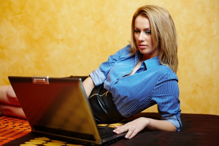 Young attractive businesswoman using her laptop in bed, after work hours photo