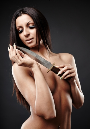 Perfect Arab woman holding a knife in her hand. Gray  background Stock Photo - 17861113