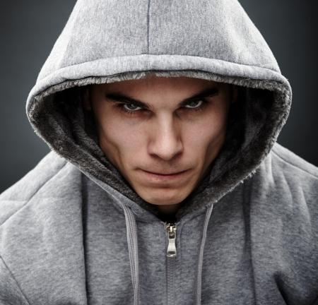 Close-up portrait de gangster menaçant vêtu d'un sweat à capuche, représentant la notion de danger