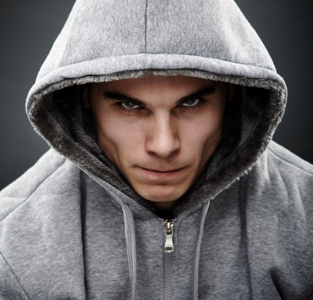 mean: Close-up portrait of threatening gangster wearing a hoodie, representing the concept of danger Stock Photo