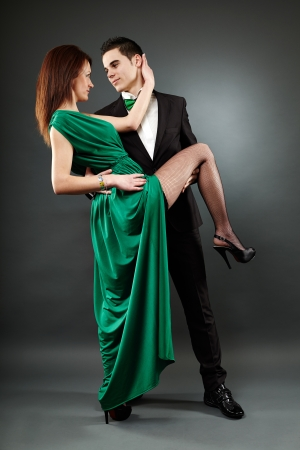 Elegant and passionate romantic couple dancing tango in full length pose photo