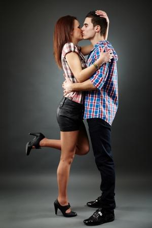 people kissing: Profil lat�ral d'un jeune couple beau embrasser et baiser sur fond gris Valentine concept Banque d'images