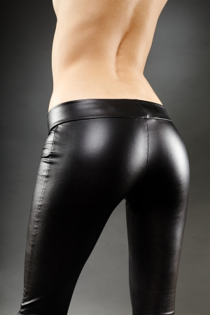 Torso of topless woman in leather pants over gray background