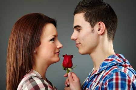 Closeup pose of young man offering a rose to the woman he loves. Valentine concept photo