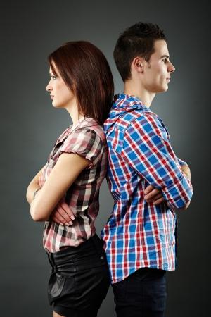 Primer plano de la joven pareja triste de pie espalda con espalda, dificultades de relación. Fondo gris
