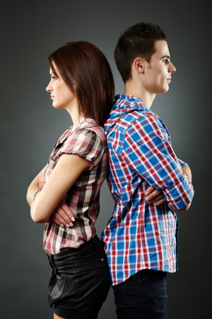 novios enojados: Primer plano de la joven pareja triste de pie espalda con espalda, dificultades de relaci�n. Fondo gris