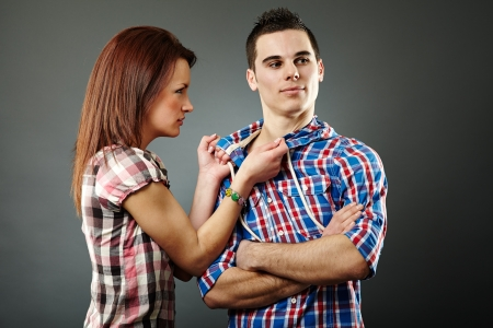 indifferent: Young woman angry with her indifferent husband. Gray background Stock Photo