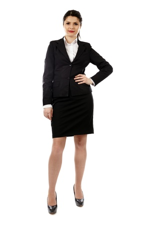 Successful young businesswoman standing with her hand in her waist in full length pose, isolated on white background photo