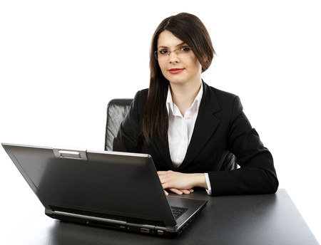 Young businesswoman sitting at her desk, with laptop, isolated on white background in closeup pose photo