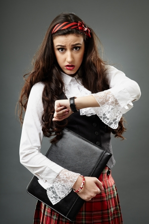 Closeup of a young shoolgirl late for school, on gray background, holding a file in her hand photo