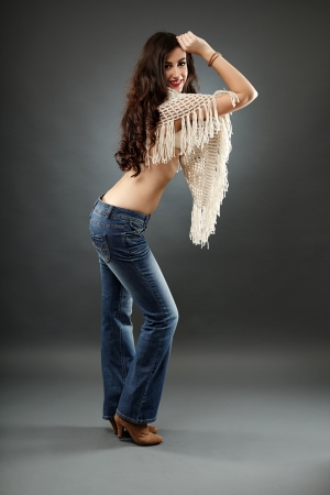 Young woman wearing a poncho and jeans, in full length pose, over gray background photo