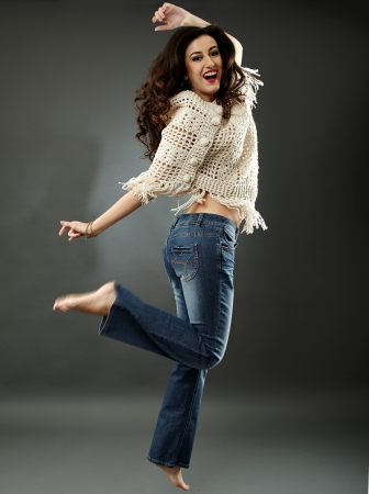 Full length pose of happy young woman, jumping of joy, on gray background photo