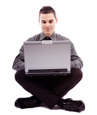 Full length pose of young businessman sitting on the floor and writing on his laptop, isolated on white background Stock Photo - 18159249