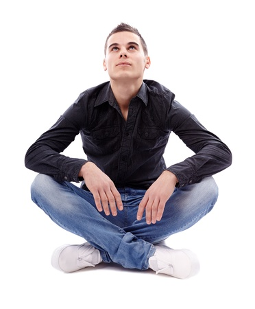 Casual young man sitting cross legged on the floor and looking up, isolated on white background Stock Photo - 18159186
