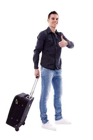 Happy young traveler carrying his luggage in full length pose, isolated on white background, thumbs up Stock Photo - 18159173