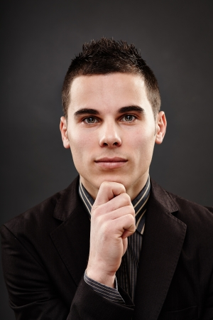 Closeup pose of a handsome young man over black background Stock Photo - 18159163