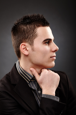Profile pose of young pensive businessman, closeup over black background Stock Photo - 18159168