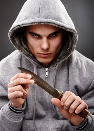 Closeup portrait of a threatening mafia man, holding a knife in his hands, over gray background, representing the concept of danger