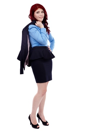 Redhead businesswoman, holding her coat over her shoulder in full length pose, isolated on white background photo
