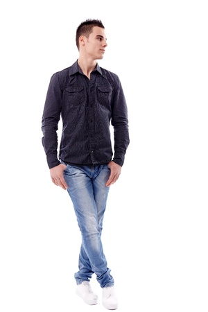 sideway: Young man standing in full length pose, isolated on white background, looking at the side of the image