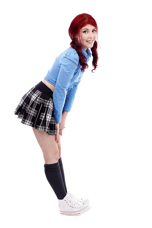 Full length pose of smiling young schoolgirl, isolated on white background photo