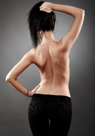Rear view of sexy brunette in closeup pose, on gray background Stock Photo - 18492010