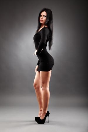Sexy jeune femme brune, vêtue d'une mini robe noire, la longueur totale glamour, sur fond gris