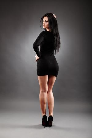 Rückansicht des sexy junge Brünette in voller Länge darstellen, auf grauem Hintergrund