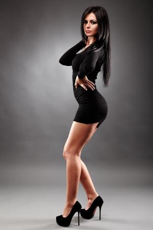 Sexy jeune femme brune, vêtue d'une robe noire mini, dans le glamour pleine longueur, sur fond gris
