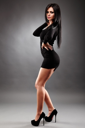 Sexy young brunette woman, wearing a mini black dress, in glamour full length, on gray background