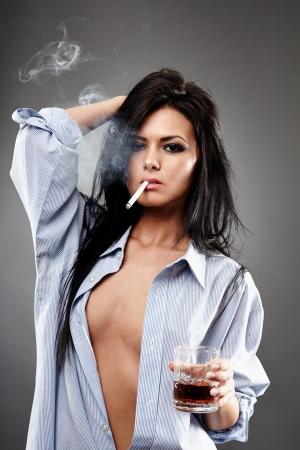 hot breast: Чувственный молодая женщина в мужской рубашки, курил сигарету и со стаканом коньяка, крупным планом позе на сером фоне, концепция разврата Фото со стока