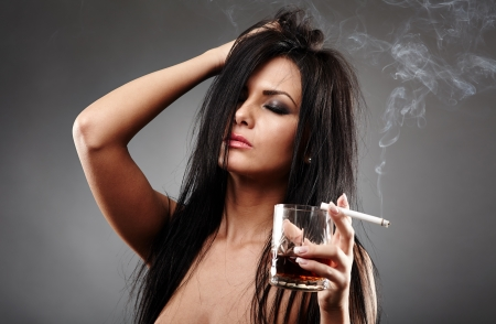 Sensual young woman with a glass of brandy and cigarette having a migraine, closeup pose over gray background Stock Photo - 18492015