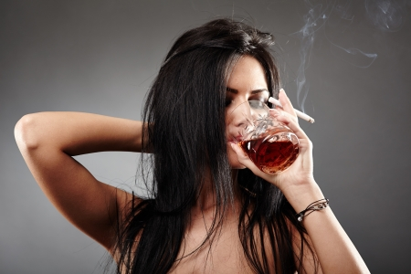 Sensual young woman drinking a glass of brandy and smoking a cigarette, closeup pose over gray background, debauchery concept Stock Photo - 18492031