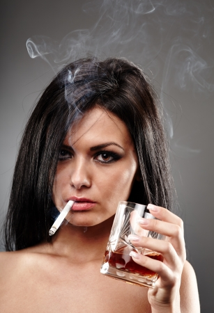 Sensual young woman smoking a cigarette and holding a glass of brandy in her hand, closeup pose on gray background, debauchery concept Stock Photo - 18492025