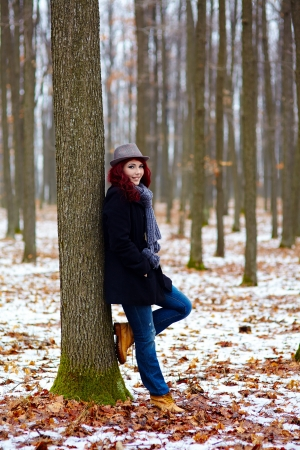 Young girl in outdoor full length, propping on a tree in a forest Stock Photo - 18492035